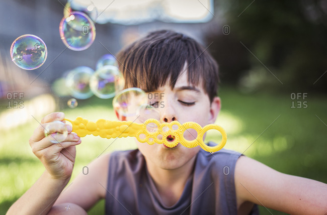 Close up of young boy blowing bubbles outdoors on a summer day.