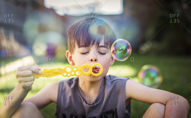 Young boy blowing bubbles outdoors on a summer day.