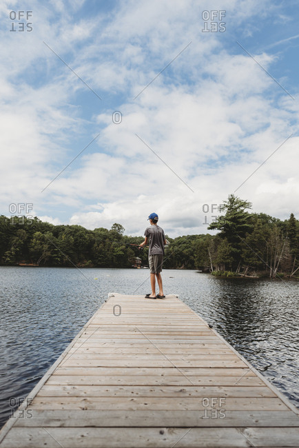 Boy fishing with a fishing rod on the end of dock on a lake in summer.