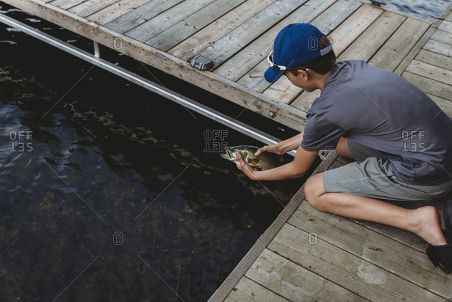 Boy releasing a fish in the water off the edge of a dock in summer.