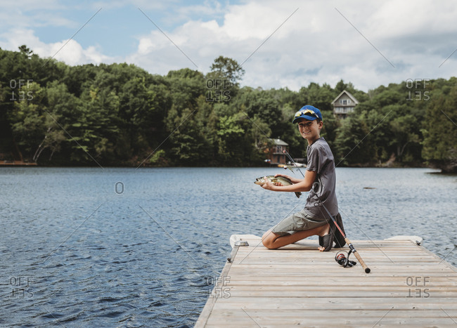 Boy holding a fish that he caught on the end of a dock on a lake.