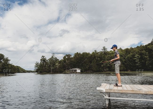 Boy fishing with a fishing rod on the end of a dock on lake in summer.