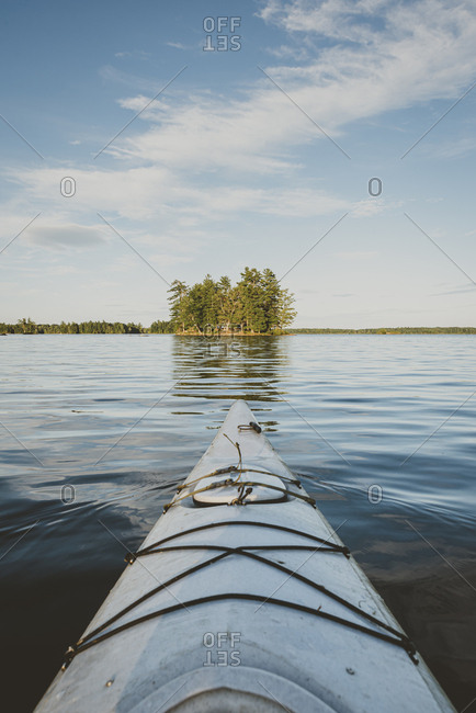 Kayaking on calm lake towards an island from point of view of paddler.