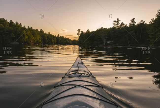 Kayaking on calm water at sunset from point of view of paddler.