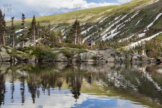 Man trail runs on lake shore in Indian Peaks Wilderness, Colorado