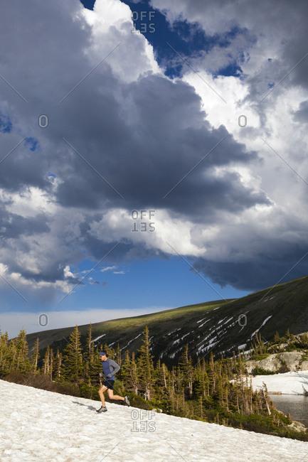 Man trail runs on snow in Indian Peaks Wilderness, Colorado