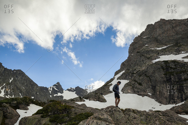 Man rests on rocks on trail run in Indian Peaks Wilderness, Colorado