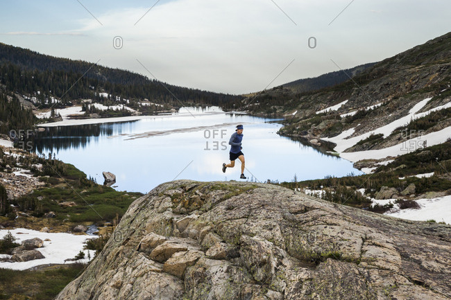 Man trail runs on rock over lake in Indian Peaks Wilderness, Colorado