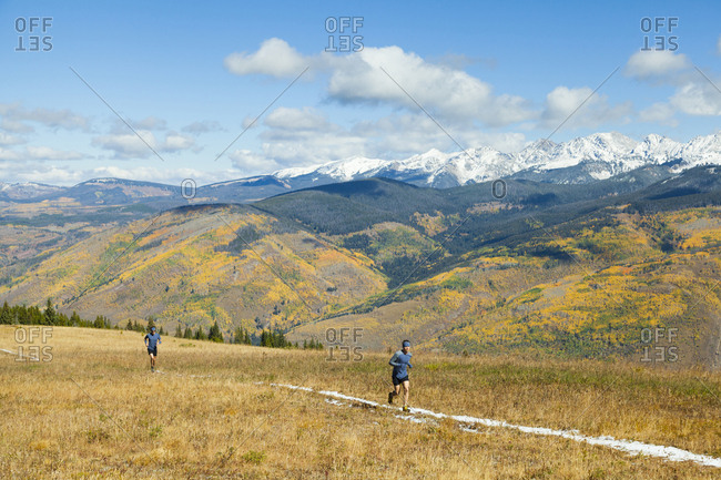 Men trail run on ridge below Gore Range mountains in Vail, Colorado