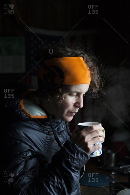 Woman skier sips hot tea inside backcountry cabin