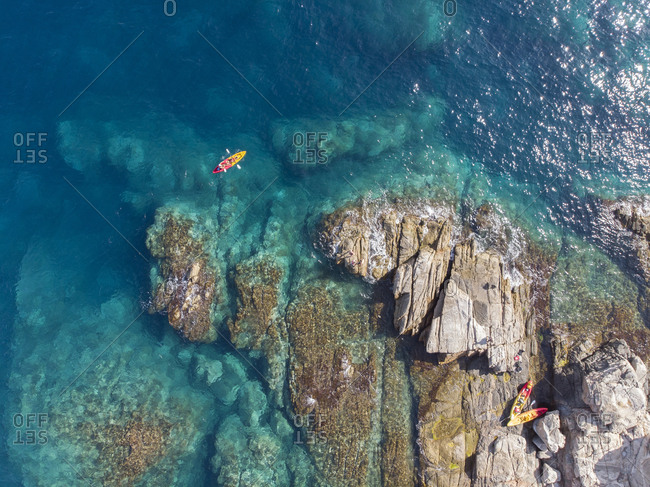 Kayakers amongst some rocks in the Mediterranean