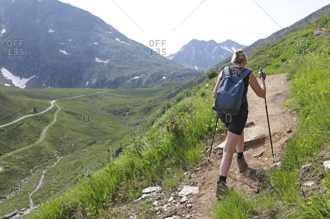 A middle aged white woman hiking along a mountainous trail in the alps