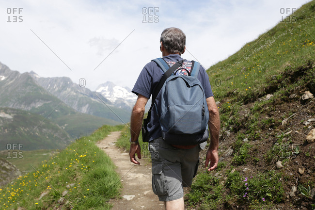 An older gentleman walking along a trail in the Swiss Alps.