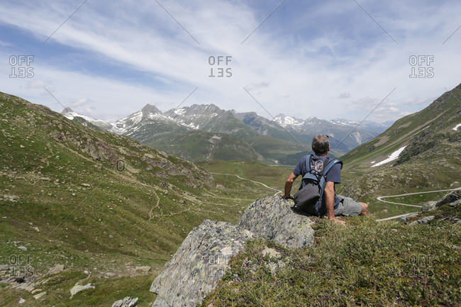 A man sitting on a rock face appreciating the alpine scenery.