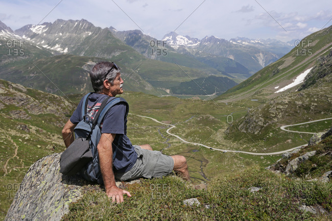 A profile shot of an older man sitting on an edge overlooking a valley