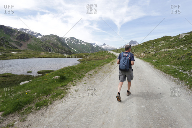 A man with a backpack walking along a gravel road in the Swiss Alps.
