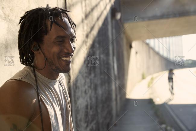 African-American man laughing wearing earbuds