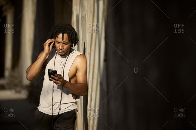 African-American man looking at phone adjusting earbuds