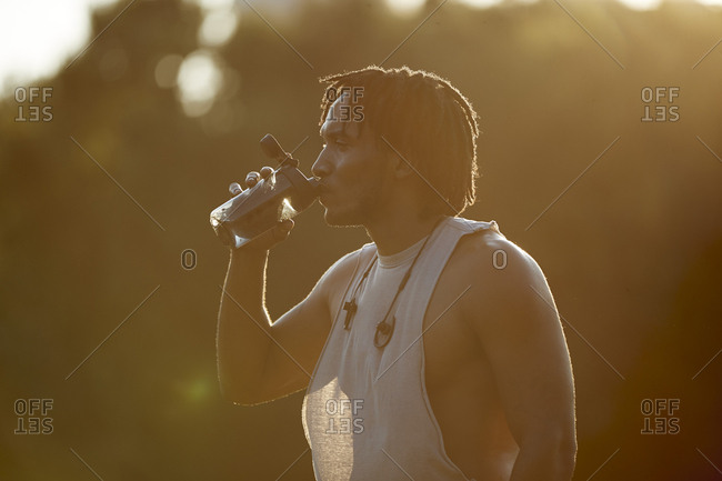 Thirsty African-American man drinking from water bottle in sunlight