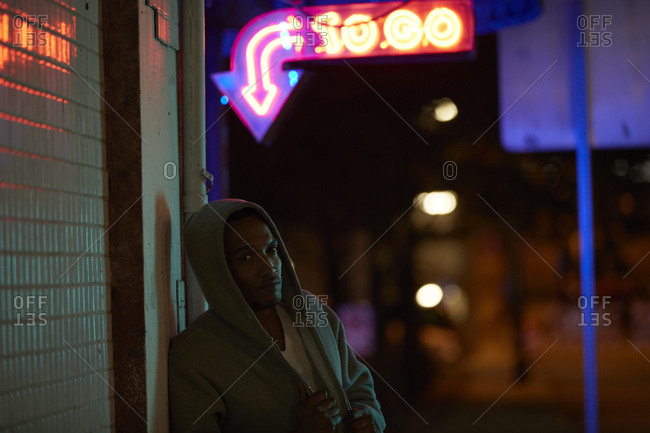 African-American man wearing hoodie under neon sign at night