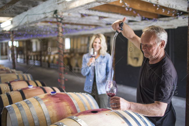sommelier extracts wine from a barrel during a wine tour.