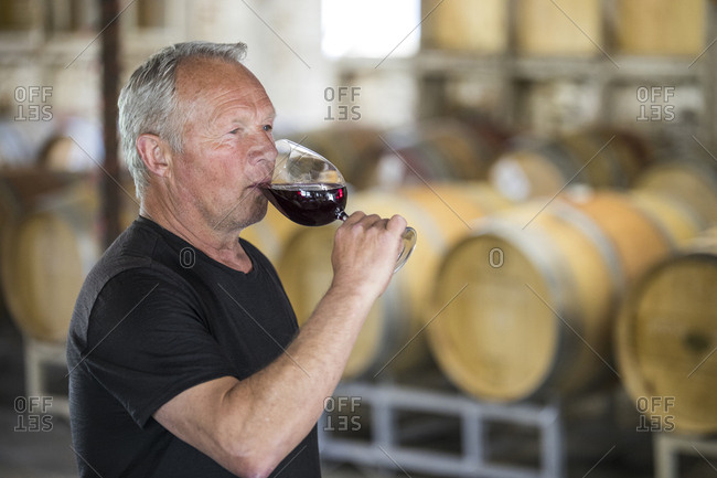 Winemaker (sommelier) sampling his product in a wine storehouse.