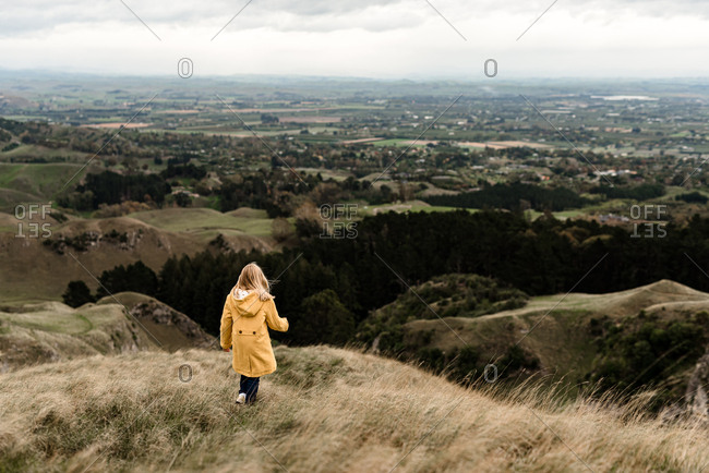 Girl in yellow jacket walking on a hilltop