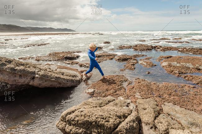 Boy stepping on rocks on the coast of New Zealand