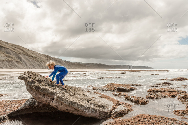 Young boy in blue wetsuit climbing on a rock at a beach