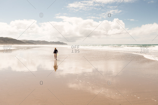 Tween girl running on beach with reflection