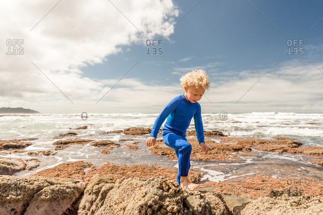 Little boy in blue wetsuit climbing rocks at a beach