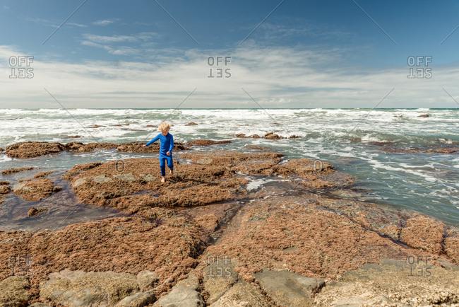 Young boy exploring the New Zealand rocky coast