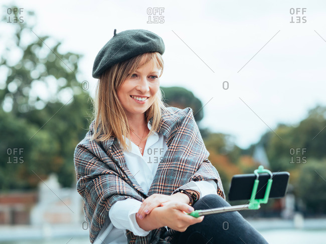 Caucasian girl with French hat takes pictures of herself with a selfie stick