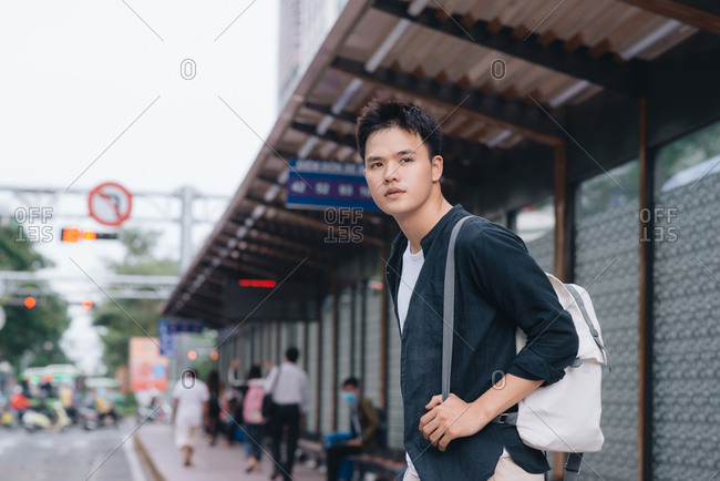 Young handsome man in shirt with hand in pocket and backpack standing near bus stop