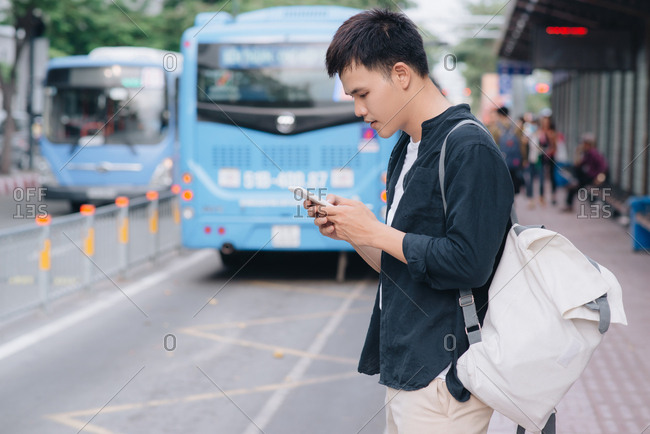 Young handsome asian man using mobile phone while waiting in bus stop