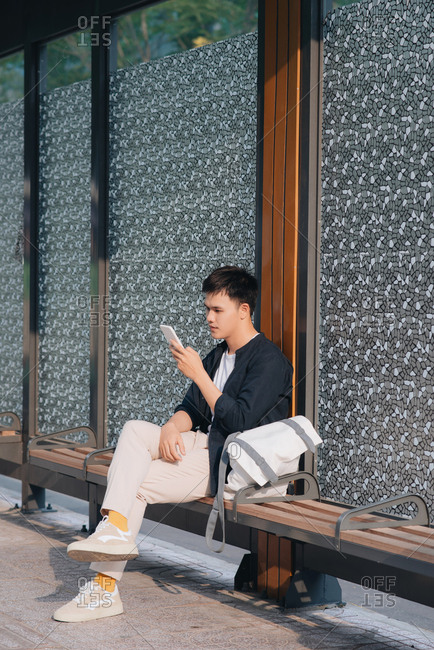 Young handsome asian man using mobile phone while waiting at bus stop
