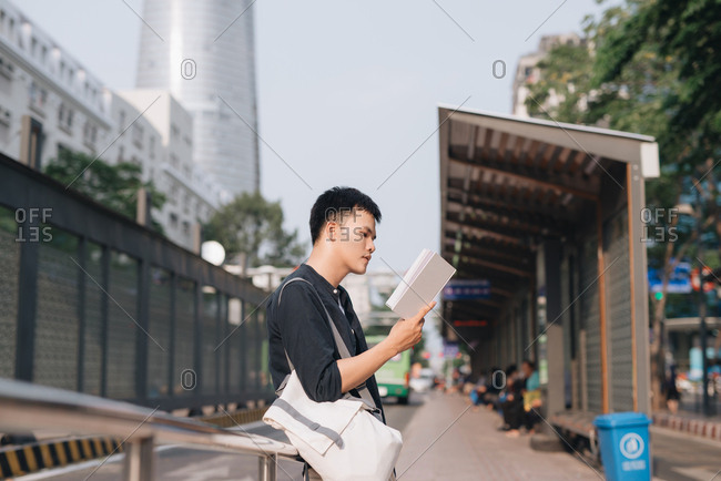 Asian tourist man backpacker waiting for bus in Ho Chi Minh city