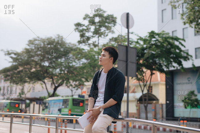 Young man waiting at bus stop, leaning on a railing in the middle of the street