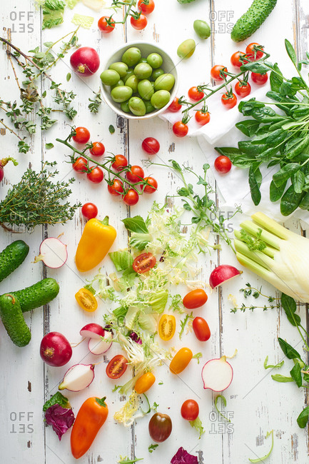 Overhead shot of vegan meal ingredients on white wooden table.