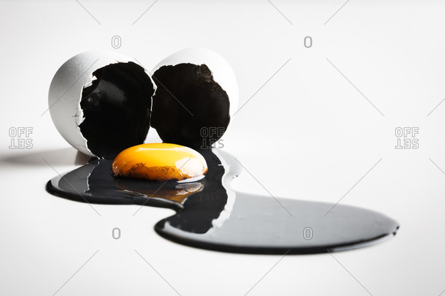 Yellow yolk and black egg white spills out of a broken egg