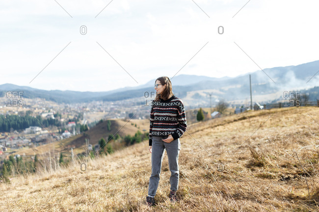 The young woman in the cozy sweater is enjoying the landscape from the foggy mountain