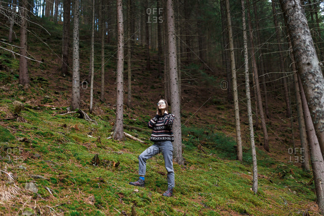 The young woman in the cozy sweater is hiking in the forest and enjoying the landscape