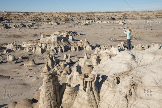 Woman snapping a photo of hoodoo sandstone rock formations Bisti/De-Na-Zin Wilderness in New Mexico.