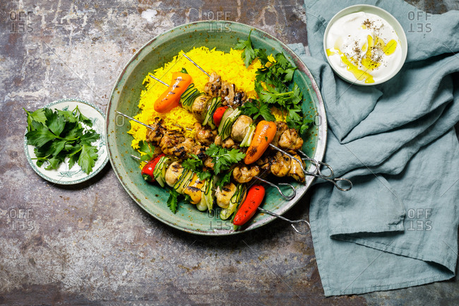 Rice marinated chicken on skewers with saffron rice