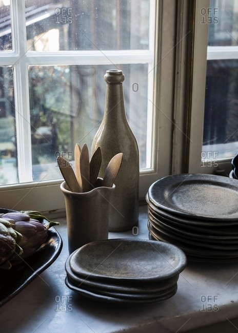 Stoneware plates and wooden utensils on counter by artichokes