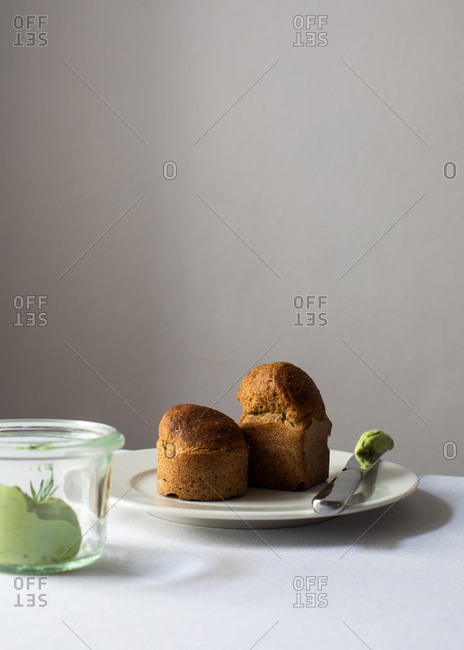 Muffin on a plate with green spread on knife