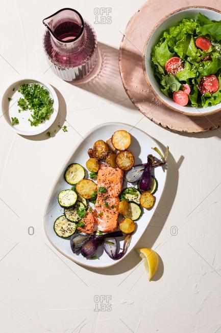 Salmon filet with veggies on plate beside salad