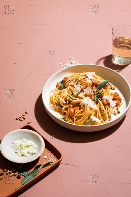 Pasta dish served with sparkling beverage on pink background