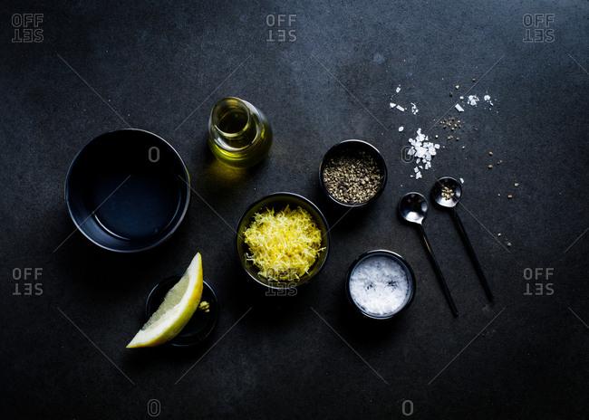 Salt, pepper, oil and lemon zest on dark background