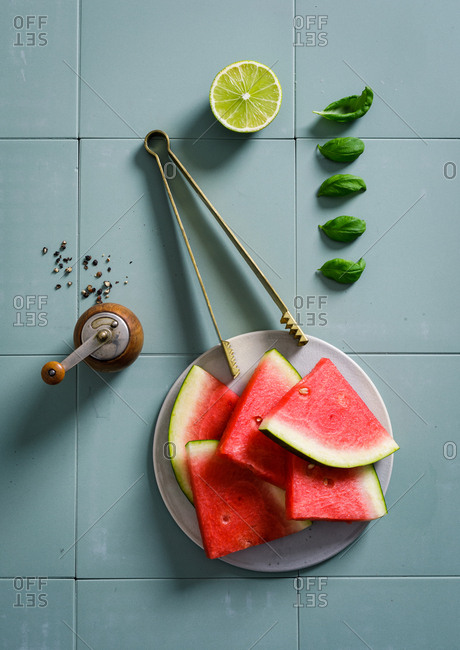 Overhead view of fresh cut watermelon slices on blue tile background